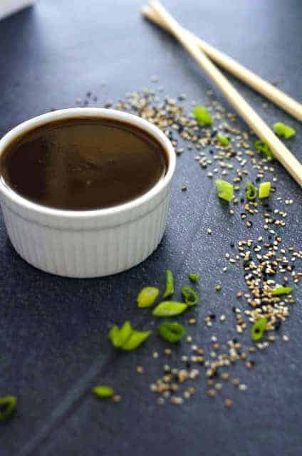 bowl of teriyaki sauce surrounded by sesame seeds, green onions and chopsticks