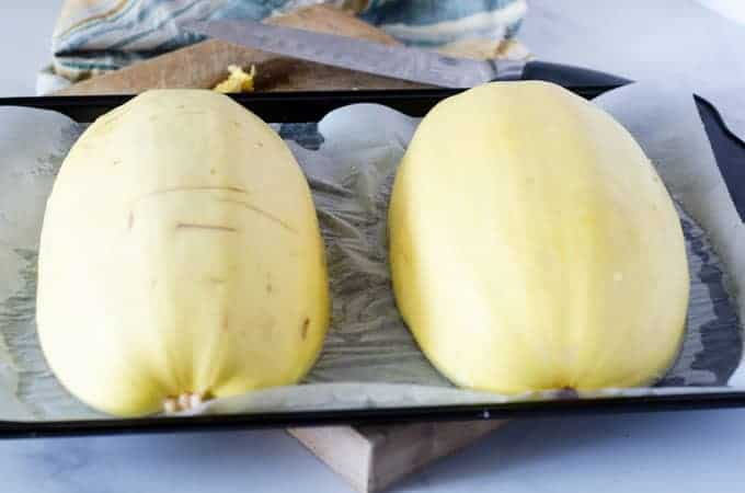 Two halves of spaghetti squash face down on a baking sheet