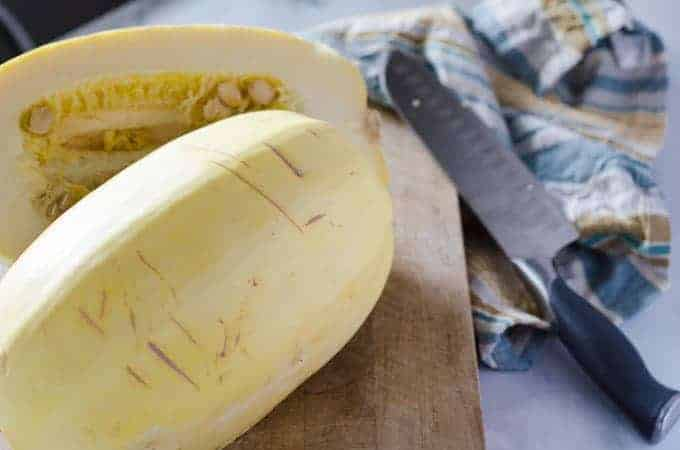 Spaghetti squash on cutting board cut in half with knife in the background