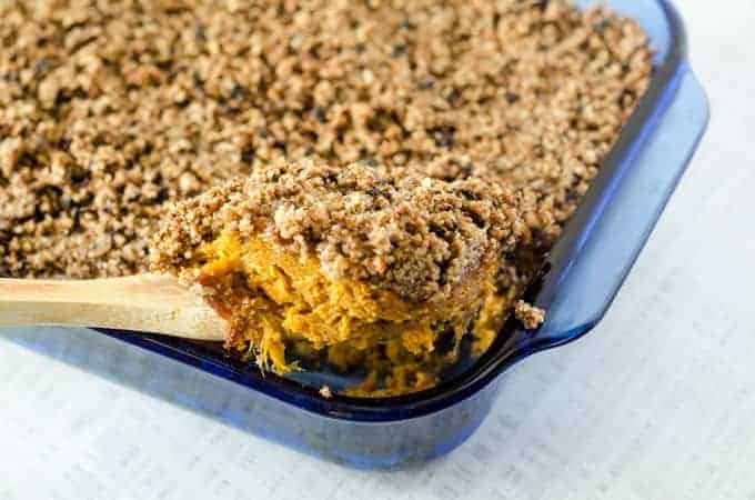 Blue casserole dish full of sweet potato casserole with spoon scooping out a serving of casserole