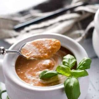 white crock of tomato basil soup with a hand holding a spoonful of soup above the dish
