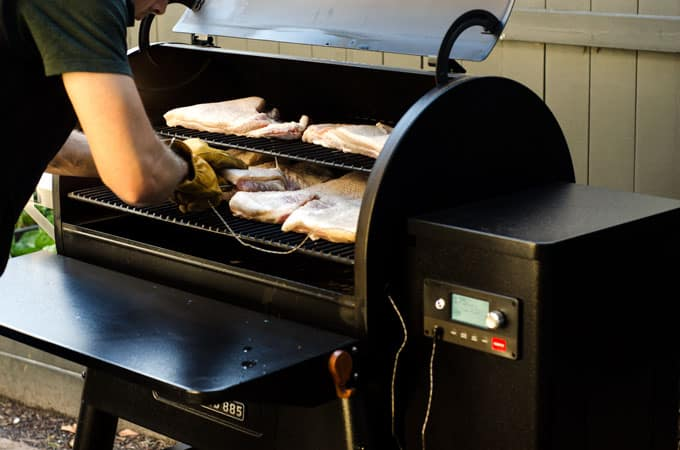 Traeger Ironwood 885 grill open with slabs of pork belly in it and man putting in meat thermometer