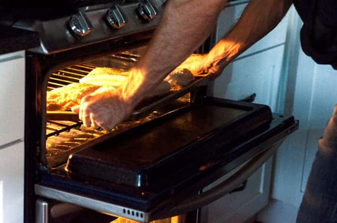 Man putting pan of pork belly into oven