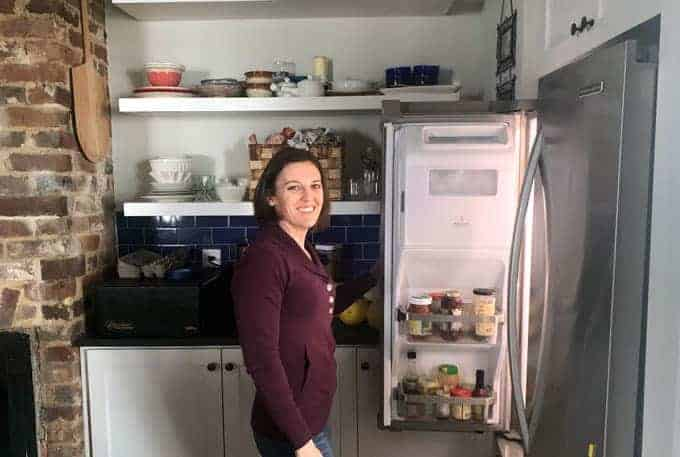 Woman standing at refrigerator holding door open and smiling
