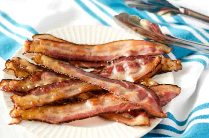 pile of bacon on a white plate on a white and blue striped towel with tongs in the background