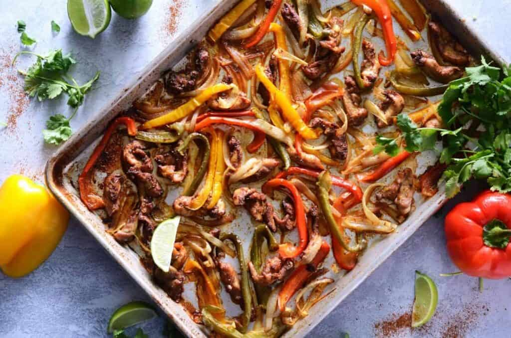 overhead view of a sheet pan covered in coked chicken, bell peppers and onions with slices of lime