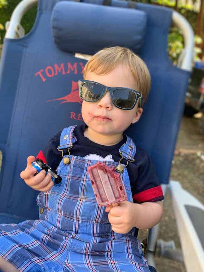 toddler sitting in lawn chair holding matchbox car in one hand and a popsicle in the other