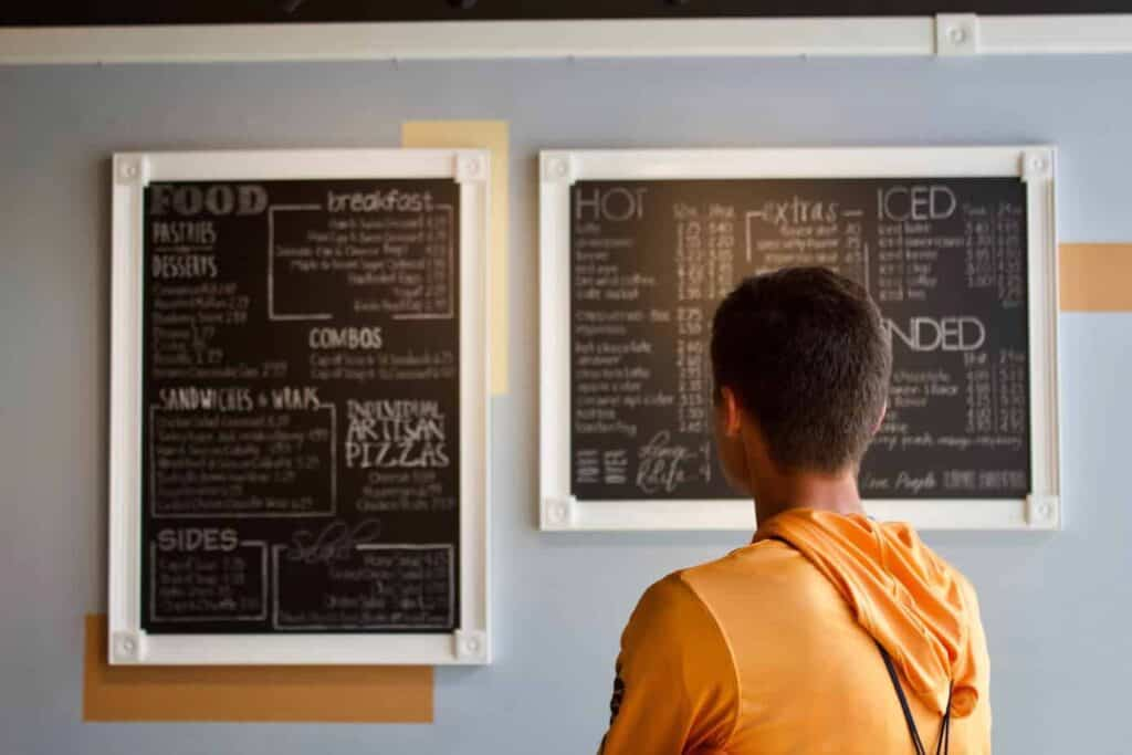 back of person's head standing looking at restaurant menu on wall