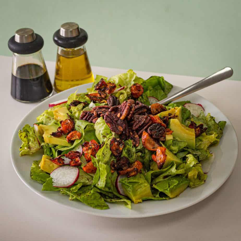 simple salad with oil and vinegar dressing next to it