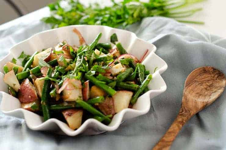 Green bean potato salad topped with fresh herbs in a white bowl with a wooden spoon next to it and fresh herbs in the background