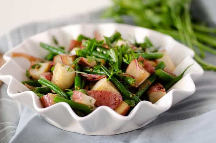 Close up of green bean potato salad in a white fluted edge bowl on top of a blue napkin with fresh herbs in the background