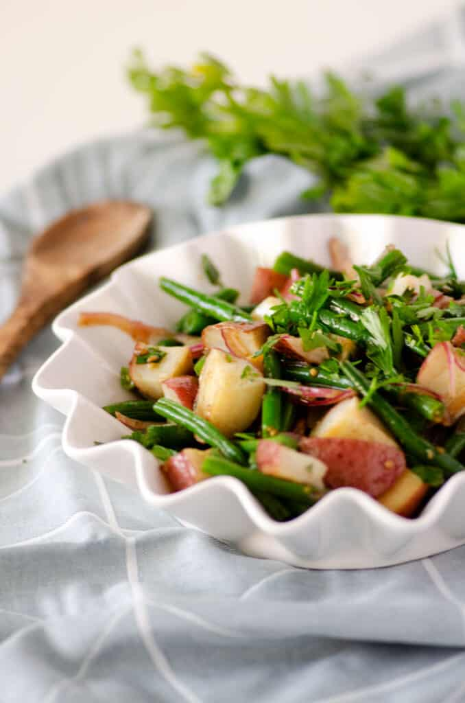 Green beans and red potatoes in a white fluted edge bowl on top of a blue napkin with wooden spoon in the background