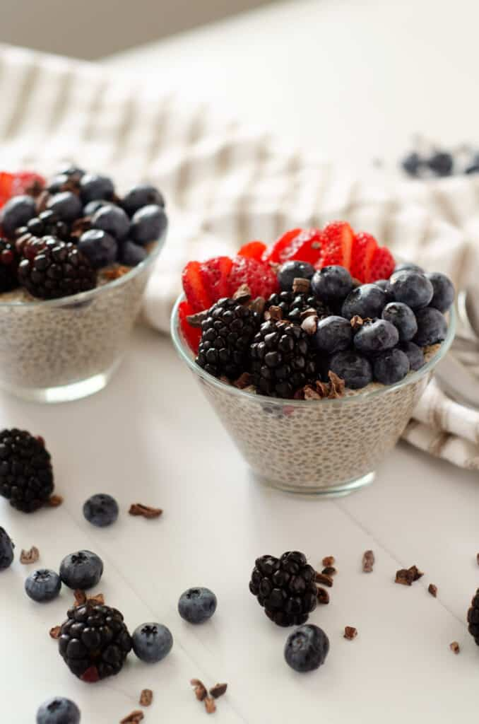 Close up of glass bowl filled with chia seed pudding with almond milk topped with fresh berries and cocoa nibs