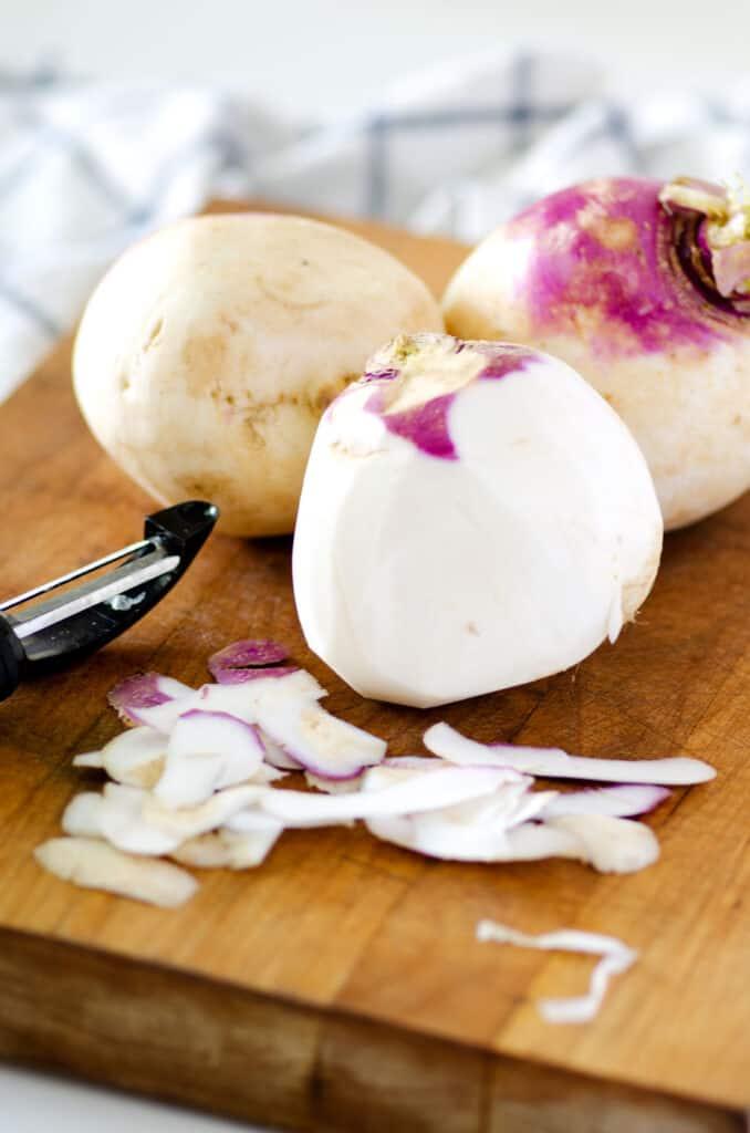 turnips on a cutting board with peeler