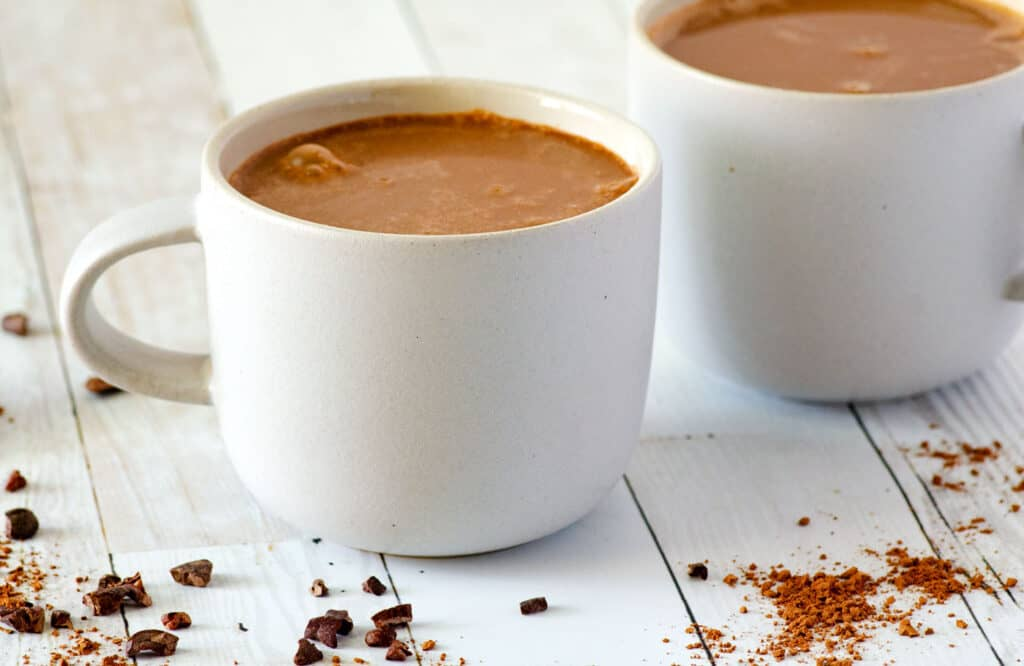 Two white coffee mugs full of homemade vegan hot chocolate on a countertop