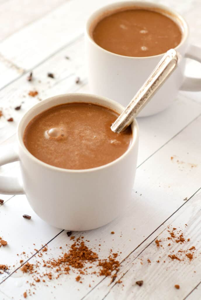 View of mug on table full of vegan hot cocoa with spoon in it