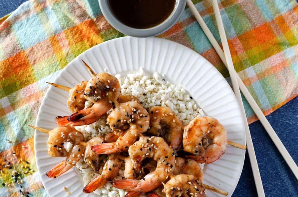 Overhead view of Traeger grilled shrimp on a plate topped with sesame seeds