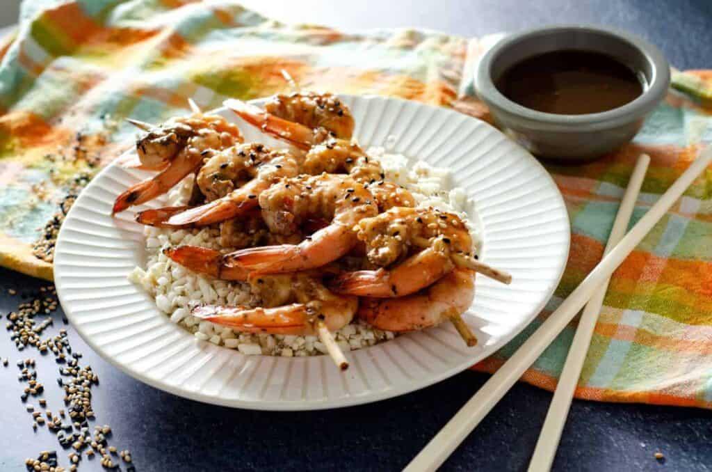 White plate with cauliflower rice and ginger teriyaki shrimp skewers