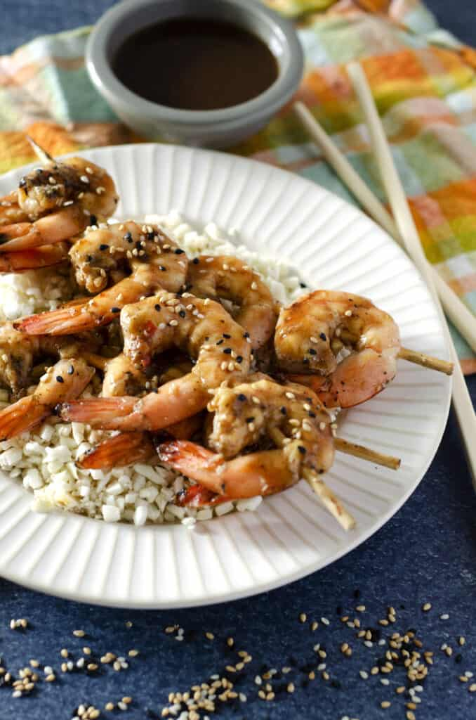 Close up of ginger teriyaki Traeger shrimp on a plate with cauliflower rice and dipping sauce