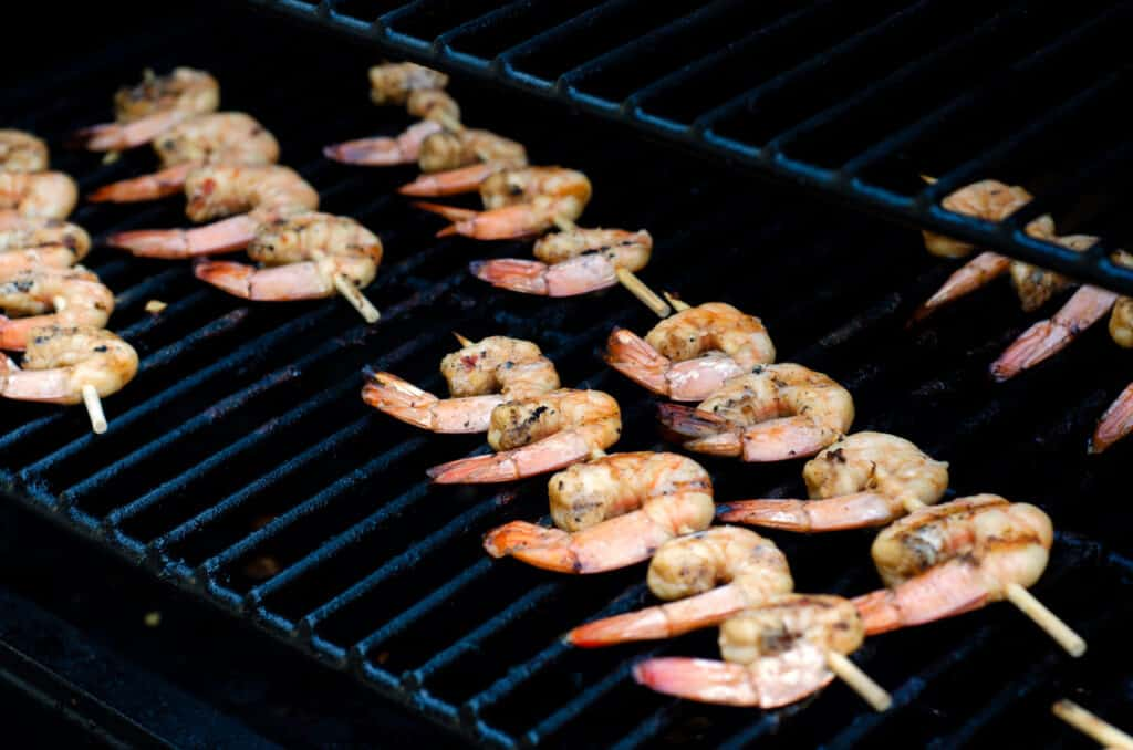 shrimp being cooked on skewers on grill