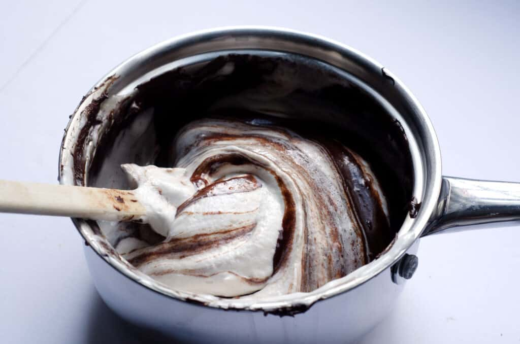 pot of melted chocolate getting coconut whipped cream folded in