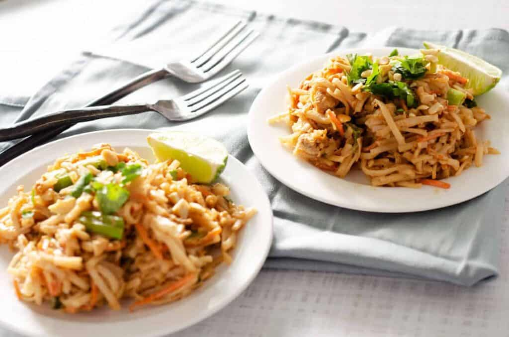 gluten free pad thai on two plates with two forks