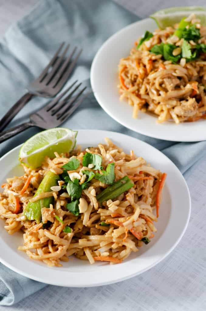 Gluten free pad thai on a plate topped with cilantro and chopped cashews with a slice of lime