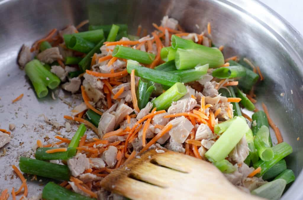 close up of stir fry pan with chicken, carrots, and green onions