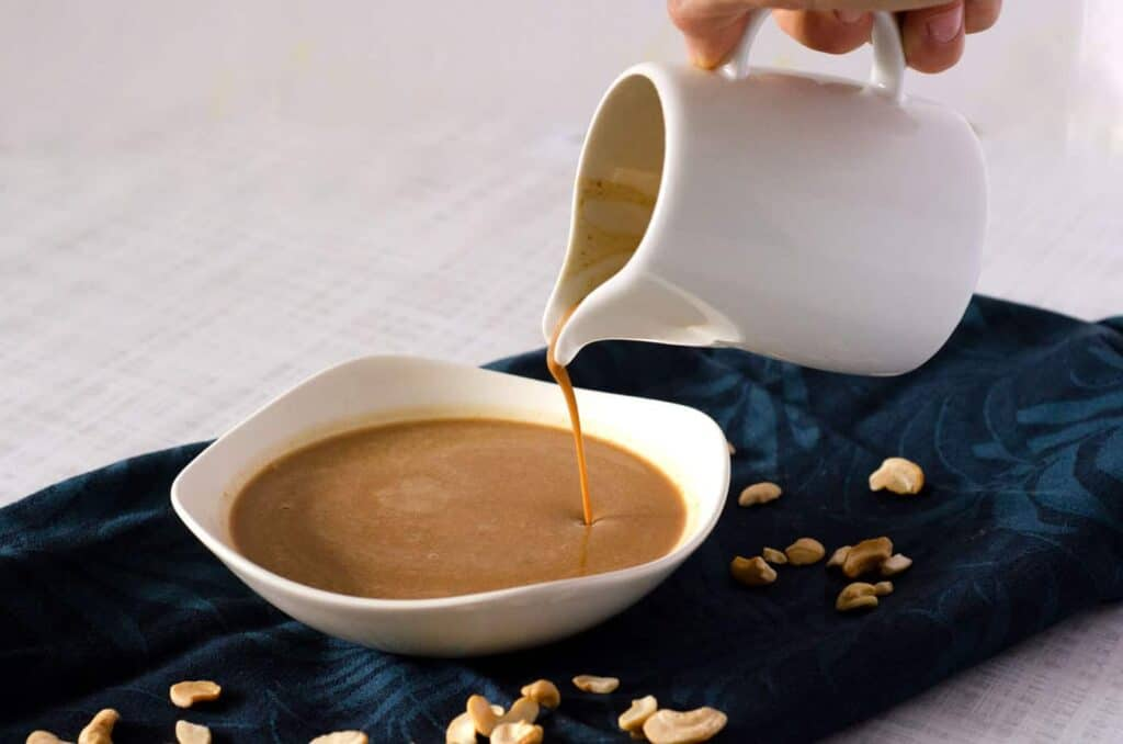hand holding a white pitcher pouring pad thai peanut sauce into a bowl