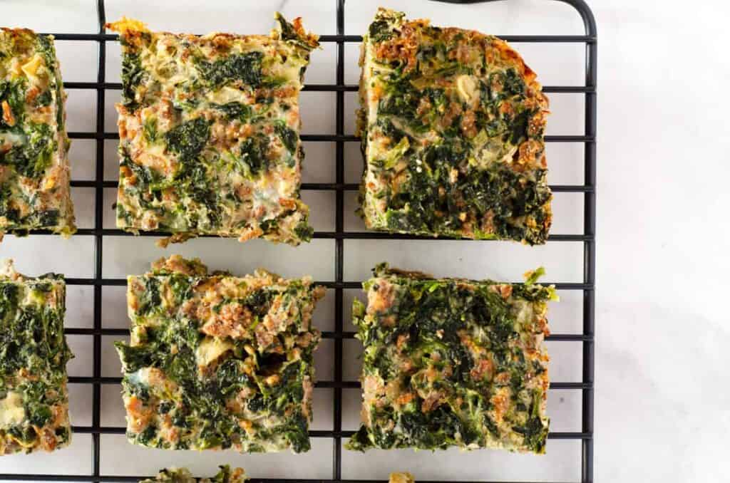 Overhead view of squares of spinach egg casserole cooling on a rack