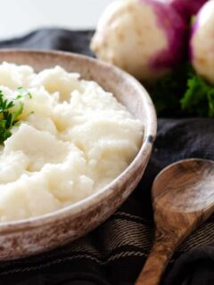 bowl of mashed turnips topped with parsley with a spoon and whole turnips in the background