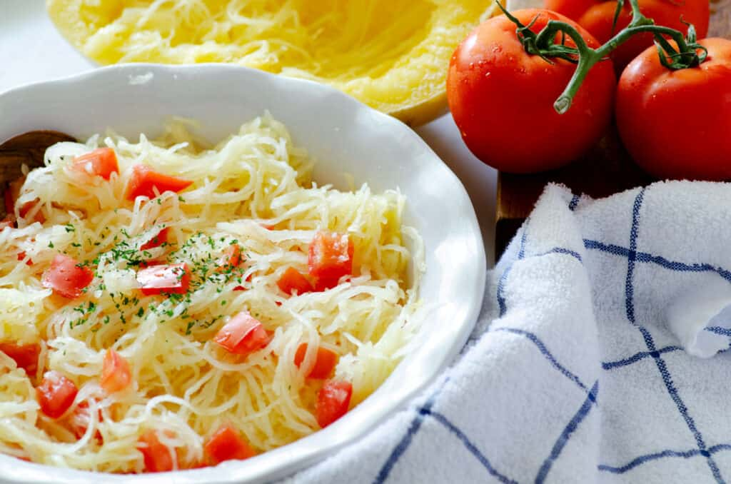 dish of spaghetti squash surrounded by a dish towel, tomatoes, and half a spaghetti squash