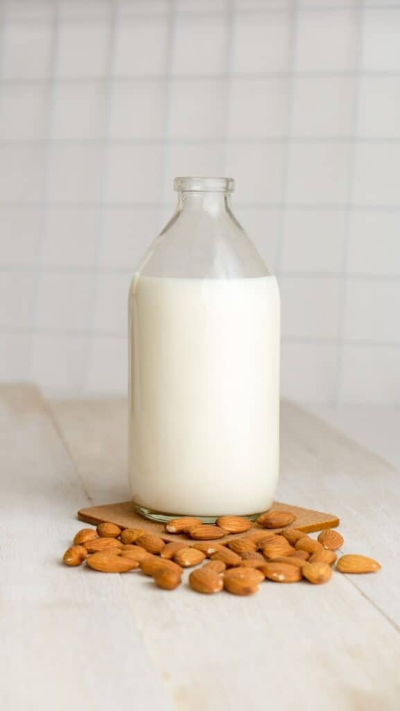 Glass bottle full of almond milk sitting on counter surrounded by almonds