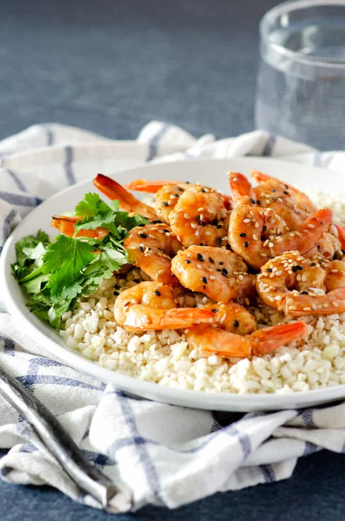 Close up of Whole30 shrimp on a plate of cauliflower rice topped with sesame seeds