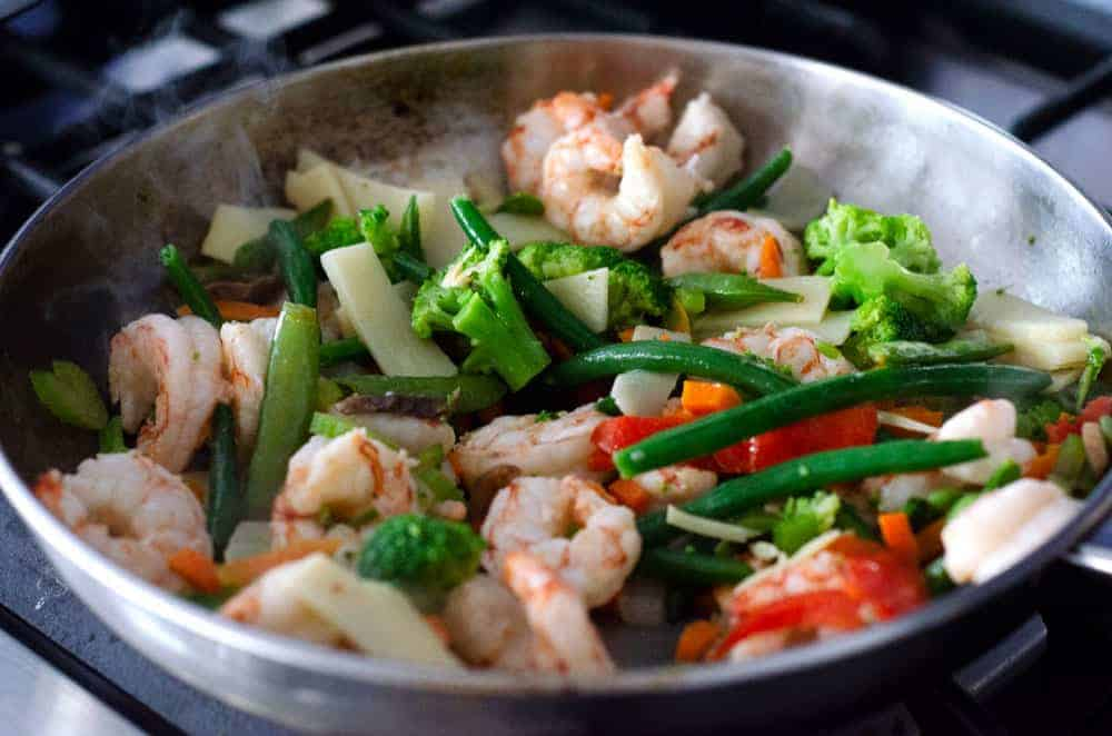 shrimp and vegetable stir fry cooking in a pan