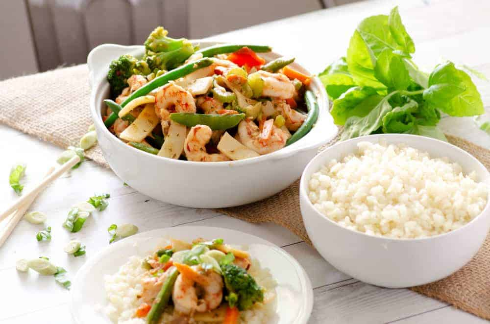 lemongrass basil paleo shrimp stir fry in a serving bowl with a bowl of cauliflower rice and a plate