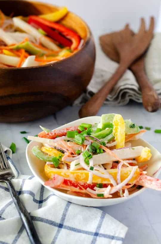 Small white bowl with fork next to it full of rainbow salad vegetables with dressing