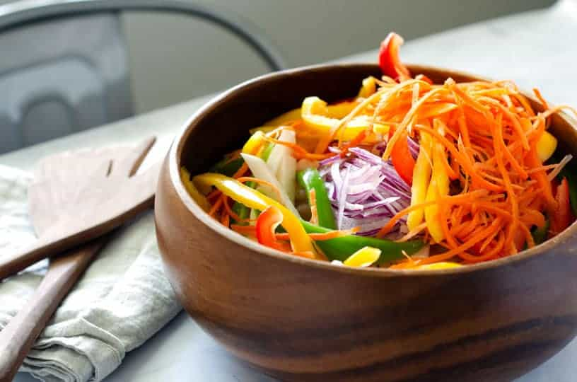 wooden salad bowl full of rainbow colored veggies