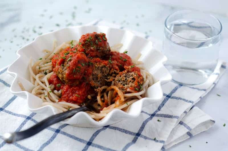 fork cutting into a paleo meatball in a bowl of cassava spaghetti
