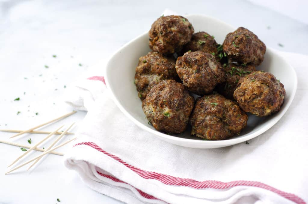 small white bowl of paleo meatballs with toothpicks nearby