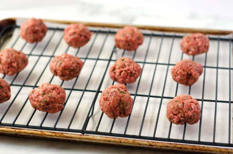 raw paleo meatballs on a baking sheet