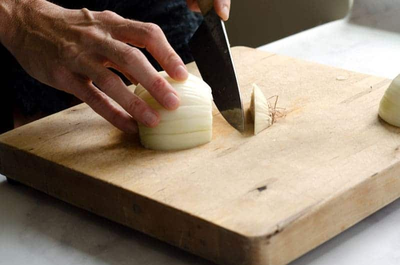 sliced onion getting root ball cut off on a cutting board