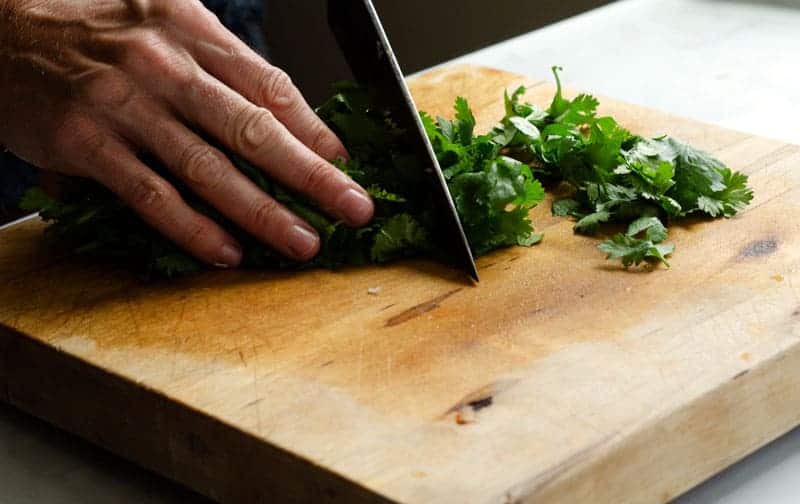 Hands on cutting board chopping cilantro with chef's knife