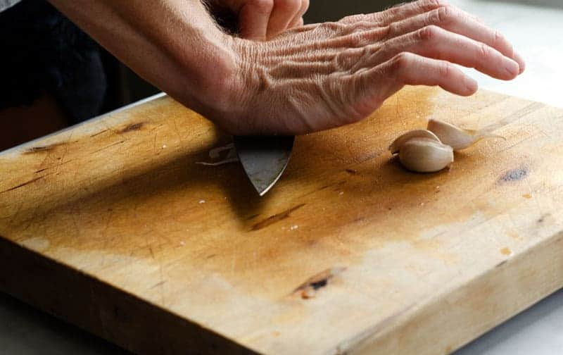 cutting board with hand pushing down on side of knife to smash a garlic clove