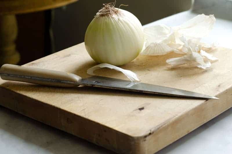 white onion peeled on cutting board with knife