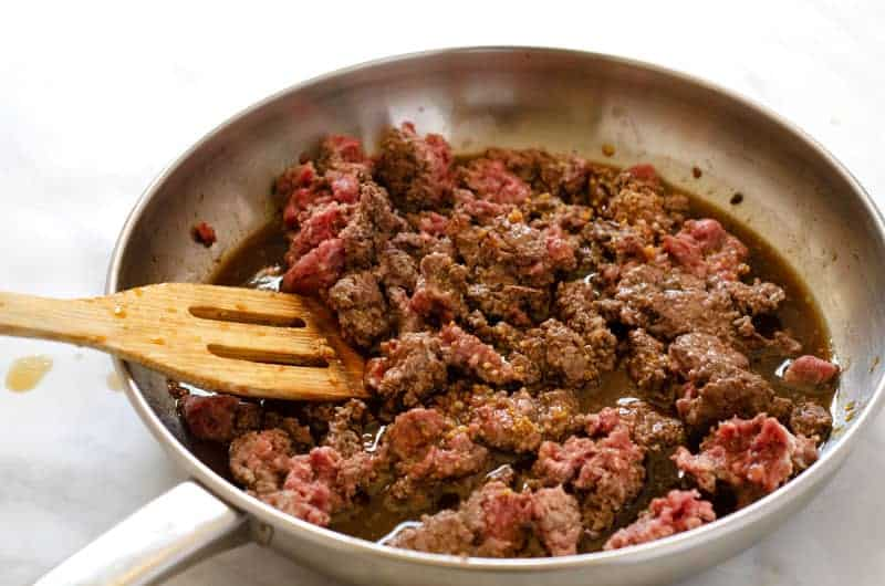 Ground beef cooking in sauce in a skillet