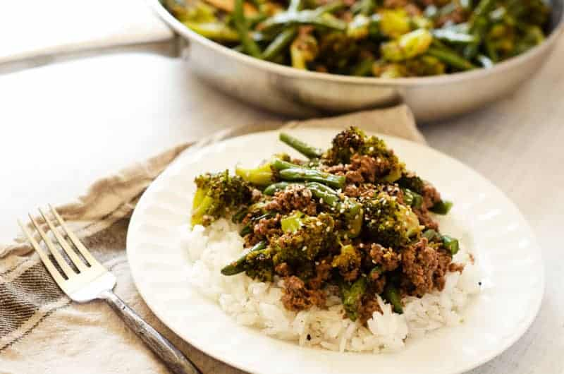 Ground beef and green beans over white rice on a plate with fork nearby