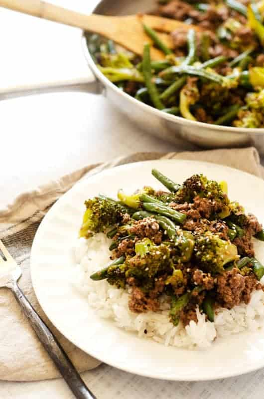 Ground beef and green beans served over rice on a white plate